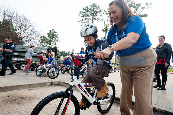Academy employee JoAnna Jones helps Zaden Farnsworth test ride his new bicycle during the annual bike donation program at Academy Sports and Outdoors in Tyler on Tuesday Dec. 18, 2018. Tyler's store donated 30 bikes and helmets that were distributed to children identified by the Tyler Police Department. The program  benefits 5,500 boys and girls at more than 120 separate donation events at Academy stores.   (Sarah A. Miller/Tyler Morning Telegraph)