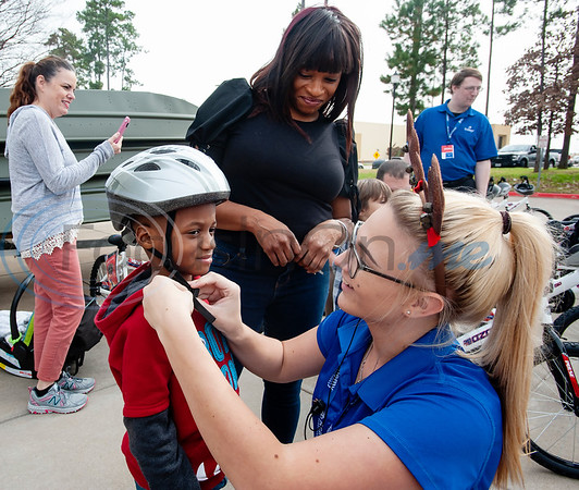 Academy employee Camryn Hunter fits a helmet for  Kingston Blackshire, 5, during the annual bike donation program at Academy Sports and Outdoors in Tyler on Tuesday Dec. 18, 2018. Tyler's store donated 30 bikes and helmets that were distributed to children identified by the Tyler Police Department. The program  benefits 5,500 boys and girls at more than 120 separate donation events at Academy stores.   (Sarah A. Miller/Tyler Morning Telegraph)