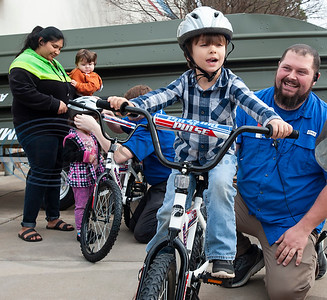 Academy employee Spencer Warren helps Preston Lennon, 4, ride his bicycle during the annual bike donation program at Academy Sports and Outdoors in Tyler on Tuesday Dec. 18, 2018. Tyler's store donated 30 bikes and helmets that were distributed to children identified by the Tyler Police Department. The program  benefits 5,500 boys and girls at more than 120 separate donation events at Academy stores.   (Sarah A. Miller/Tyler Morning Telegraph)