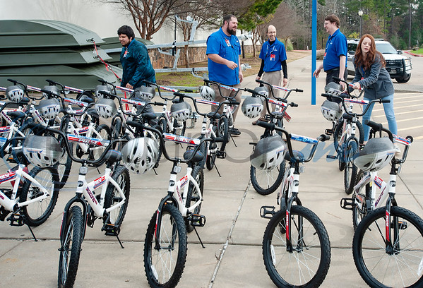 Academy employees get bicycles and helmets ready for 30 children test ride and take home during the annual bike donation program at Academy Sports and Outdoors in Tyler on Tuesday Dec. 18, 2018. Tyler's store donated 30 bikes and helmets that were distributed to children identified by the Tyler Police Department. The program  benefits 5,500 boys and girls at more than 120 separate donation events at Academy stores.   (Sarah A. Miller/Tyler Morning Telegraph)