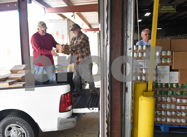 Garth Campbell, Gerald McVay and Mike Simpson load a truck with 5,000 pounds of food headed to the Community Food Pantry of Noonday Monday Dec. 12, 2016 at the East Texas Food Bank in Tyler. The East Texas Food Bank serves 26 counties by providing food to nearly 200 partner agencies to distribute to those in need.   (Sarah A. Miller/Tyler Morning Telegraph)