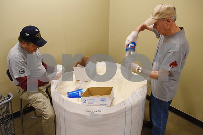 Volunteers David Pierson and Dick Gibson repackage rice at the East Texas Food Bank Monday Dec. 12, 2016 in Tyler.  (Sarah A. Miller/Tyler Morning Telegraph)