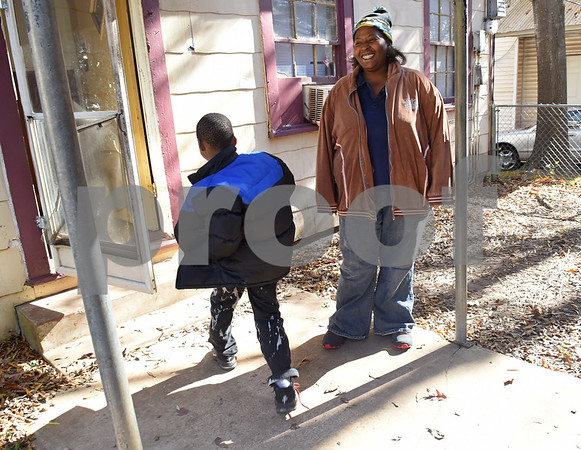Chevon Andrews smiles as her son Da'Veon Thomas, 7, walks into their new home Monday Dec. 19, 2016 in Tyler. The family had previously been staying at the Salvation Army homeless shelter.   (Sarah A. Miller/Tyler Morning Telegraph)