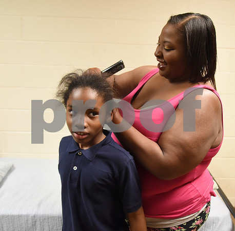 Chevon Andrews combs her son KeiVonta's hair in their room at the Salvation Army homeless shelter Thursday Dec. 15, 2016.  (Sarah A. Miller/Tyler Morning Telegraph)