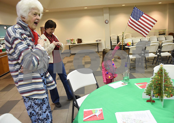 Volunteer Ruby Shumway, 5, holds the United States flag as participants and helpers recite the Pledge of Allegiance during the Alzheimer's Alliance's Wonderful Wednesdays program Wednesday Dec. 14, 2016. Wonderful Wednesdays is a day club program that provides cognitive and social stimulation for individuals in the early or mid-stages of Alzheimer's disease and related dementias. It also serves as a break time for families and caregivers.   (Sarah A. Miller/Tyler Morning Telegraph)