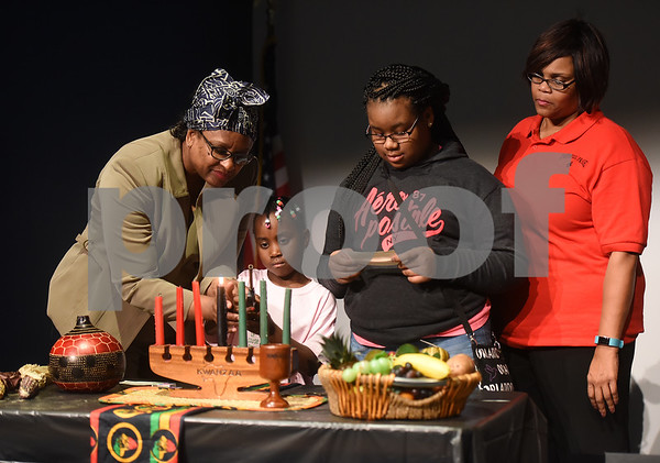 Pat Record-Henry, Asia Sanders, 7, Anicia Clark, 11, and Charlotte Sanders participate in lighting the candles representing the seven principals of Kwanzaa during the Kwanzaa celebration at the Tyler Public Library Wednesday night Dec. 28, 2016.  (Sarah A. Miller/Tyler Morning Telegraph)