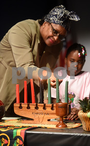 Pat Record-Henry and Asia Sanders, 7, light the candles representing the seven principals of Kwanzaa during the Kwanzaa celebration at the Tyler Public Library Wednesday night Dec. 28, 2016.  (Sarah A. Miller/Tyler Morning Telegraph)