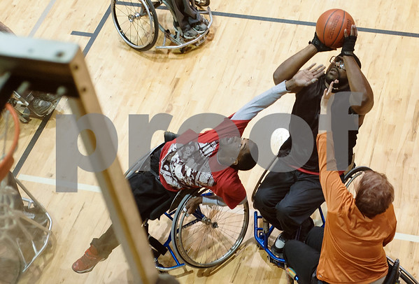 "Jarvin Dorsey of Tyler aims for a basket with defenders Dewartha ""T.J."" Scott of Tyler, left, and Mandy Crenshaw of Mineola, right, blocking during Tyler Thorns practice at First Christian Church in Tyler Tuesday Dec. 29, 2015. Tyler Thorns are a wheelchair basketball team that competes in Division III of the National Wheelchair Basketball Association.  (Sarah A. Miller/Tyler Morning Telegraph)"