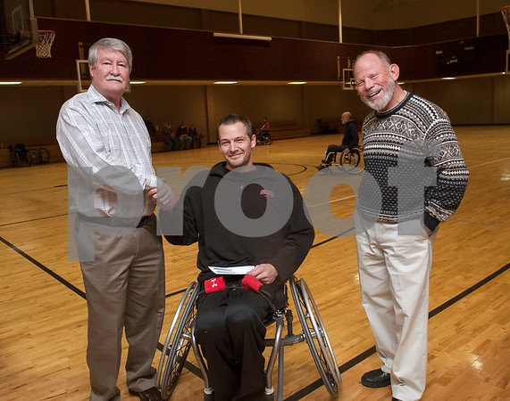 First Christian Church representatives Wayne Aaron, left, and Dale Barton, right, present Tyler Thorns coach Francis Key with a donation during Tyler Thorns practice at First Christian Church in Tyler Tuesday Dec. 29, 2015. Tyler Thorns are a wheelchair basketball team that competes in Division III of the National Wheelchair Basketball Association.  (Sarah A. Miller/Tyler Morning Telegraph)