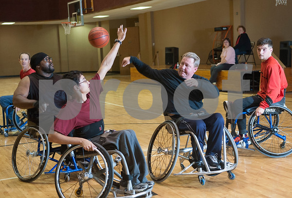 Stephen Washburn of Kilgore, right, passes the ball past Dylan Bright of Troup during Tyler Thorns practice at First Christian Church in Tyler Tuesday Dec. 29, 2015. Tyler Thorns are a wheelchair basketball team that competes in Division III of the National Wheelchair Basketball Association.  (Sarah A. Miller/Tyler Morning Telegraph)