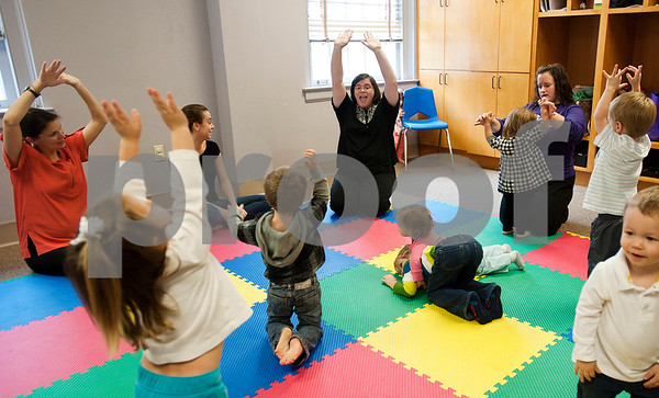 photo by Sarah A. Miller/Tyler Morning Telegraph  Amy Williams, Kindermusik teacher in training, center, leads the class in a song where they lift their arms high and low during  Kindermusik class Friday Nov. 8 at First Presbyterian Church in Tyler. Kindermusik is an early childhood music and movement program.