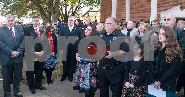 Laura Petty carries a folded United States flag as her husband Smith County Precinct 5 Constable Kevin carries the ashes of K-9 officer Ogar after the memorial service for the dog Saturday Jan. 23, 2016 held at First Baptist Church in Lindale, Texas. K-9 officer Ogar was slain while chasing a suspect after a traffic stop Tuesday Jan. 19. Several hundred people came to the memorial including many area K-9 handlers and officers. Ogar had been with Constable Kevin Petty for a little more than a year. Pictured at right are the couple's daughters Isabella Petty, 8, and Savannah Petty, 13.  (Sarah A. Miller/Tyler Morning Telegraph)