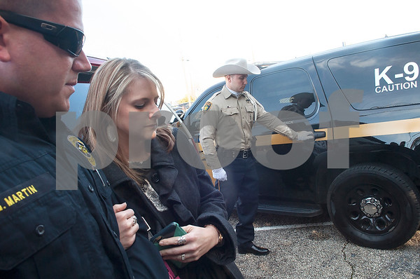 Smith County Sheriff's Office Deputy Nathan McMillan closes the vehicle door after after Smith County Constable Kevin Petty placed the ashes of his K-9 partner Ogar inside the vehicle at the conclusion of the memorial service for Smith County K-9 officer Ogar Saturday Jan. 23, 2016 held at First Baptist Church in Lindale, Texas. K-9 officer Ogar was slain while chasing a suspect after a traffic stop Tuesday Jan. 19. Ogar had been with Smith County Constable Kevin Petty for a little more than a year. Pictured at left are Tyler Police officer Garrett Martin and wife Melody Martin.  (Sarah A. Miller/Tyler Morning Telegraph)
