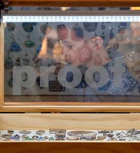 A child is seen through a reflection in a glass jewelry case  at the East Texas Gem and Mineral Society's 22nd annual jewelry, rock, mineral and fossil show at the Tyler Rose Garden Center on January 26, 2018. The show continues through Jan. 28.  (Sarah A. Miller/Tyler Morning Telegraph)