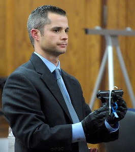 Detective Craig Beckjord holds the handgun found hidden in the ceiling at Which Wich during Kevin McGregor's trial at the Boulder County Justice Center in Boulder, Colorado January 27, 2012.  McGregor is charged with the murder of Todd Walker in March of 2011. CAMERA/MARK LEFFINGWELL