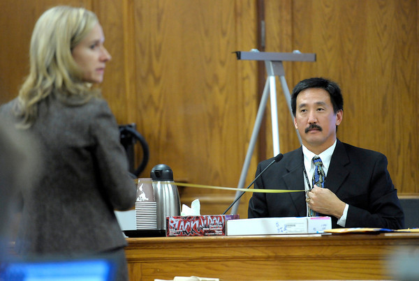 Prosecutor Karen Lorenz (left) and Agent Gale Higashi (right), firearm examiner of the Colorado Bureau of Investigation, hold a tape measure between them to demonstrate the probable distance the muzzle from the firearm that killed Todd Walker was from him when discharged during Kevin McGregor's trial at the Boulder County Justice Center in Boulder, Colorado January 27, 2012.  McGregor is charged with the murder of Todd Walker in March of 2011. CAMERA/MARK LEFFINGWELL