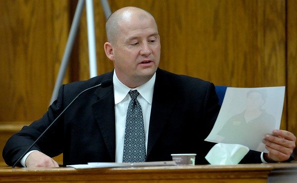 Detective Kurt Foster looks at a photo he took of Kevin McGregor during Kevin McGregor's trial at the Boulder County Justice Center in Boulder, Colorado January 27, 2012.  McGregor is charged with the murder of Todd Walker in March of 2011. CAMERA/MARK LEFFINGWELL