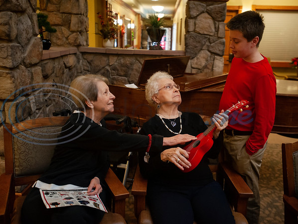 Atria Willow Park residents Judy Lippert and Earnestine Garrett learn about playing the ukulele from All Saints Episcopal School student Connor Kirkpatrick, 10, at the senior living community in Tyler on Friday Dec. 7, 2018. The All Saints Episcopal School Advanced Ukulele Ensemble and Singers played Christmas songs at Atria Willow Park as well as Boshears Center for Exceptional Programs School on Friday.   (Sarah A. Miller/Tyler Morning Telegraph)