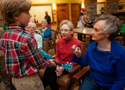 All Saints Episcopal School student Brazos Mazzare, 11, explains how to play a ukulele to Atria Willow Park residents Connie Nichols and Johnie Phillips at the senior living community in Tyler on Friday Dec. 7, 2018. The All Saints Episcopal School Advanced Ukulele Ensemble and Singers played Christmas songs at Atria Willow Park as well as Boshears Center for Exceptional Programs School on Friday.   (Sarah A. Miller/Tyler Morning Telegraph)