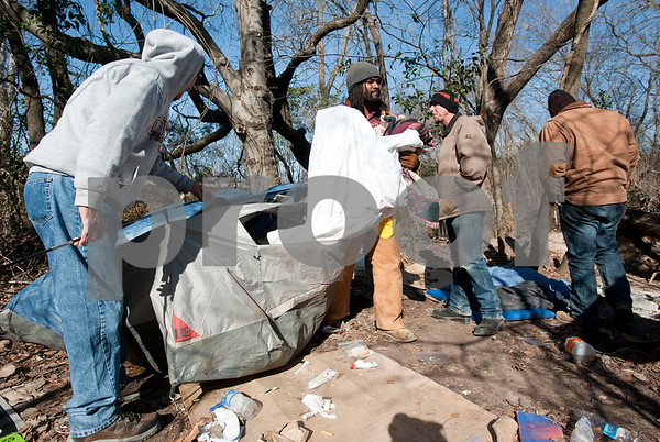 photo by Sarah A. Miller/Tyler Morning Telegraph  Volunteers from various homeless ministries and non-profit organizations help to clean up the wooded area known as Tent City in Tyler Tuesday after homeless men and women were told to leave this camping area which is on Union Pacific property Monday night.