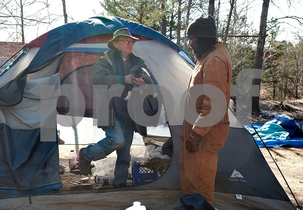 photo by Sarah A. Miller/Tyler Morning Telegraph  Tyler Tent City resident Bobby Campbell, left, holds his cat Gizmo as Church Under A Bridge associate pastor John Walton, right, helps him clean up and remove his tent Tuesday. Campbell has been living in the wooded area since Feb. 2013 and is not sure where he will relocate his tent.