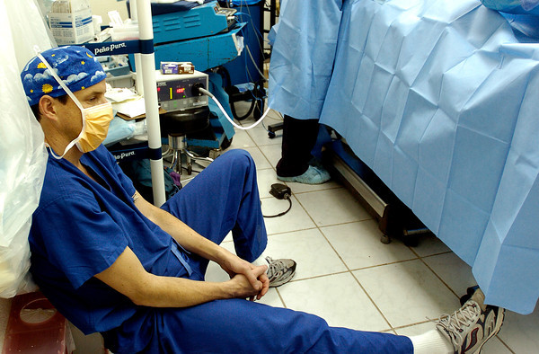 Dr. Goeff Lighthall , an anesthesiologist, takes a break on a stool in one of the three operating rooms after finishing a surgery at Hospital Civil on Feb. 9, 2005. The general surgery teams would routinely work 12 hour days, at times 14 hours, trying to help as many patients as possible in the seven days of the medical campaign.<br /> Photo by Joshua Lawton / Daily Camera / Wednesday, Feb 9, 2005