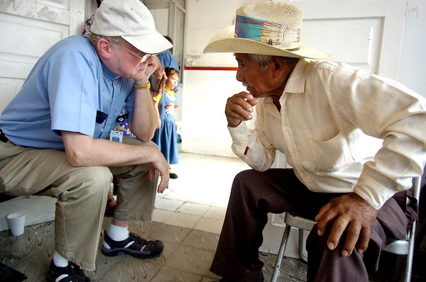 Father David Kenny, director of pastoral services left, talks with Pedro Zapata Gutierrez, 84, in the Mante Red Cross while waiting for his wife to have eye surgery on Feb. 9, 2005. <br /> Photo by Joshua Lawton / Daily Camera / Wednesday, Feb 9, 2005