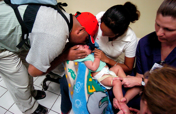 Emmanuell Jimenez , left, kisses the forehead of his seven month-old son, Angel Jimenez , in the lap of the boy's mother, Maria del Carmen Martinez , while in the recovery room after having a procedure to repair a bilateral cleft lip. <br /> Photo by Joshua Lawton / Daily Camera / Wednesday, Feb 9, 2005
