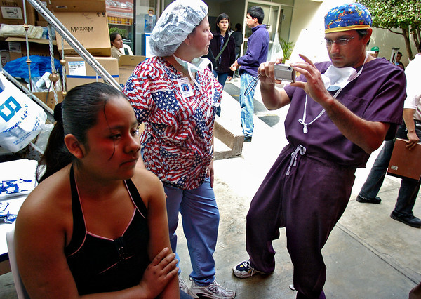 Dr. Sarvjit Gill, right, takes a photo of Yolanda Almazan, a 15 year-old from a town of indigenous people near Tampico, Mexico, who has a tumor in her sinus cavity as Jodelle Myhre, center watches other activities in at Hospital Civil on Feb. 6, 2005. Dr. Dill proposed bringing Almazan to his surgery center in Loveland to perform the surgery. <br /> Photo by Joshua Lawton / Daily Camera / Sunday, Feb 6, 2005