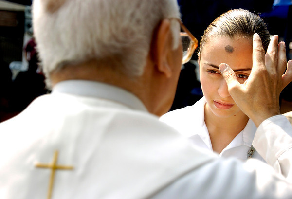 Anai Estrada , a nursing student assisting at the eye clinic, looks at Padre Victor Carranza during a ceremony for Ash Wednesday on Feb. 9, 2005. The strong Christian and Catholic culture of Mexico is reflected in everyday life; the ceremony symbolizes penitence for the start of Lent.<br /> Photo by Joshua Lawton / Daily Camera / Wednesday, Feb 9, 2005