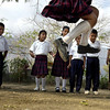 A girl sails past fellow students of Ignacio Lopez Rayon Elementary School during a contest for the physical exercise portion of class on Feb. 8, 2005. The object of the game was to see who could jump the farthest using two sticks as markers.<br /> Photo by Joshua Lawton / Daily Camera / Tuesday, Feb 8, 2005