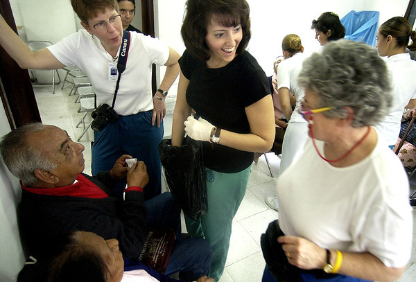 Dr. Debra Firestone, center, reacts after opening a bag with a gift of tequila from a man she had operated on the previous day, as Debby Shields , right, moves in to see the bottle inside the eye clinic on Feb. 8, 2005. Patients give tokens of appreciation, from tequila to cookies, to members of the Boulder team.<br /> Photo by Joshua Lawton / Daily Camera / Tuesday, Feb 8, 2005