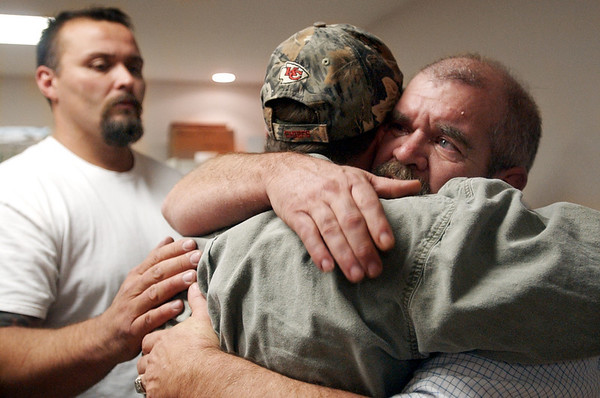 Globe/T. Rob Brown<br /> Dave Norris of Seneca, right, receives a hug from Gary Starchman of Purdy as Steve Box of Pierce City also adds some comfort during a recovery meeting Sunday, Nov. 27, 2006, at Shoal Creek Revival Church east of Granby.