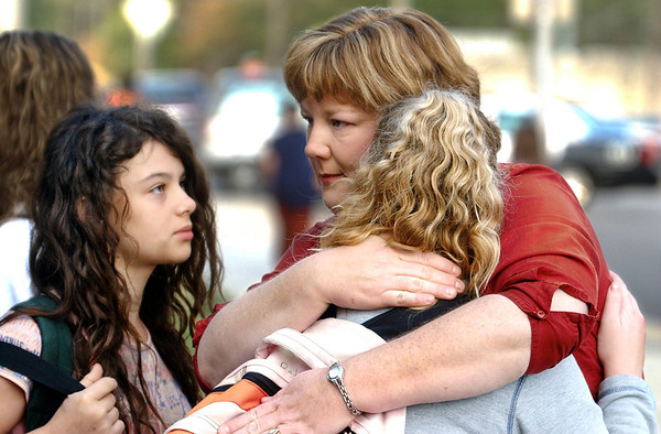 Globe/T. Rob Brown<br /> Lori Herron, Memorial Middle School science teacher, comforts Bethany Drew as Ashley Bilke, both seventh graders, look on Monday morning, Oct. 9, 2006, in front of Memorial Middle School following an incident involving an armed student. The girls were waiting for their parents to pick them up.