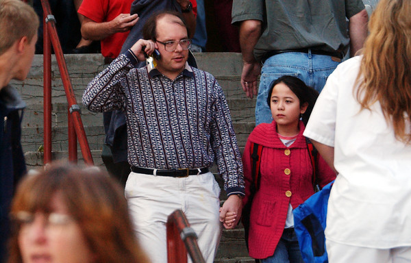 Globe/T. Rob Brown<br /> Daniel Baker of Joplin holds his daughter's hand as he calls his wife to let her know they're both safe as they walk down the front steps from Memorial Middle School Monday morning, Oct. 9, 2006, following an incident involving an armed student.<br /> Section: News