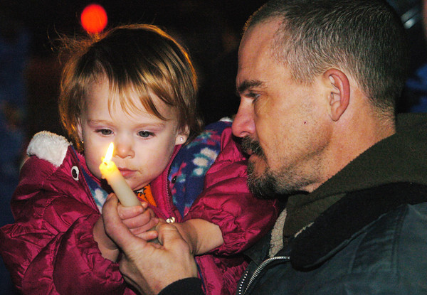 Globe/T. Rob Brown<br /> Larry Henson of Pineville helps his daughter Olivia Henson, 1, hold a candle during a candlelight vigil outside the remains of the group home fire in Anderson Monday night, Dec. 4, 2006.<br /> Section: News