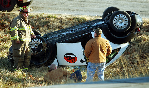 Globe/T. Rob Brown<br /> Seneca firefighters and others look over an overturned Geek Squad Volkswagon Beetle, owned by Best Buy, just off Missouri Route 43 approximately 2 miles north of Seneca following a motor vehicle accident Monday afternoon, Jan. 23, 2006.<br /> RECORDS