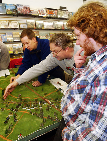 "Globe/T. Rob Brown<br /> Philip Wilson of Joplin, right, ponders his next move as Nathan Asmus of rural Joplin, left, and Chris Wilkowski of Carthage, the game master, play a turn of the game ""Eagles to Glory,"" a historical miniatures wargame. In this scenario they are in the Battle of Trebbia from the Napoleonic Wars in Northern Italy in 1799 during the Quarterly Game Day at Changing Hands Book Shoppe on Virginia Street in Joplin, Saturday afternoon, Feb. 4, 2006.<br /> Section: T&C WED Story: Derek"