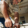 Globe/T. Rob Brown<br /> Tommy Howerton repairs a lawnmower in preparation for this weekend's citywide Neosho yard sale as seen in this photo taken Monday afternoon, March 27, 2006, outside his Neosho home.<br /> Section: News Story: Linda