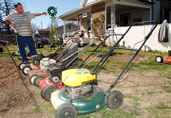 Globe/T. Rob Brown<br /> Tommy Howerton looks over a selection of lawnmowers he recently repaired in preparation for this weekend's citywide Neosho yard sale as seen in this photo taken Monday afternoon, March 27, 2006, outside his Neosho home.<br /> Section: News Story: Linda