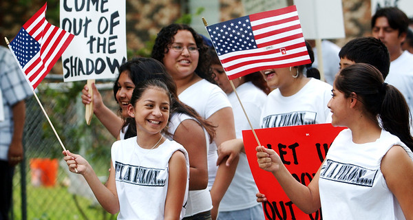 "Globe/T. Rob Brown<br /> A large group of immigrants march down a residential street in downtown Noel Monday afternoon, May 1, 2006, wearing T-shirts that read, ""I'm a felon..."" holding U.S. flags and signs that read sayings like, ""Let us come out of the shadow,"" ""We pay taxes too,"" and ""I am my parents' American dream.""<br /> Section: News"