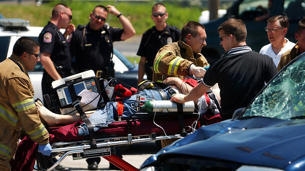Globe/T. Rob Brown<br /> Emergency personnel carry an injured person to an ambulance following a motorycle and vehicle collision at the intersection of 7th and Florida streets Friday afternoon, June 9, 2006.<br /> Section: News