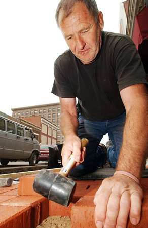 Globe/T. Rob Brown<br /> Darel Biggers of Fairgrove, a landscaper with C&S Landscaping of Fairgrove, hammers one of approximately 24,000 ornamental sidewalk bricks into place on Main Street in downtown Joplin Wednesday afternoon, April 26, 2006. The landscaping crew reported they were laying around 300 yards of bricks on each side of Main Street between Fourth and Sixth streets, which covers approximately 4,700 square feet.<br /> Section: News Story: unknown -- community shot?