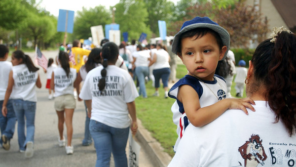 "Globe/T. Rob Brown<br /> Abel Parra, 2, (right) is held by his mother, Maria Devora of Southwest City, as a large group of immigrants march down a residential street in downtown Noel Monday afternoon, May 1, 2006, holding U.S. flags and signs that read sayings like, ""Let us come out of the shadow,"" ""We pay taxes too,"" and ""I am my parents' American dream.""<br /> Section: News"