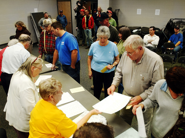 Globe/T. Rob Brown<br /> After waiting in a long line in the hallway outside the band room, which serves as a voting room, voters such as David Haralson make it to the front of the line to receive a ballot from Election Judge Lucille Myers, both of Carl Junction, at Carl Junction High School Tuesday evening, Nov. 7, 2006.<br /> Section: News