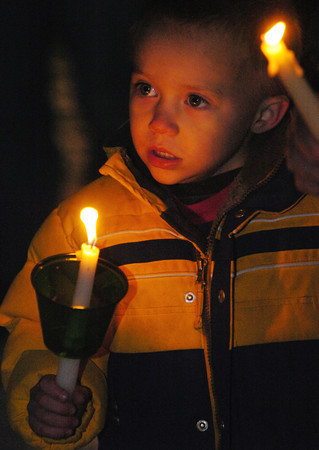 Globe/T. Rob Brown<br /> Mac Henson, 4, son of Larry and Carla Henson of Pineville, holds a candle during a candlelight vigil outside the remains of the group home fire in Anderson Monday night, Dec. 4, 2006.<br /> Section: News