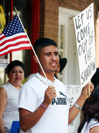 "Globe/T. Rob Brown<br /> Abelardo Guerrero, 17, of Southwest City, holds up a U.S. flag and a sign that reads, ""Let us come out of the shadow,"" as a group of immigrants prepare for a march in downtown Noel Monday afternoon, May 1, 2006.<br /> Section: News"
