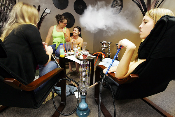 Globe/T. Rob Brown<br /> Patrons Erica Schwartz, left, and Jenny Spencer, right, both of Joplin share a hookah with chocolate mint flavored tobacco Thursday night, May 31, 2007, at 12:51 Hookah Lounge on 7th Street in Duquesne, Mo. Sheri Stephens, next to right, and Dana Frazier, both of Carthage, try another variety in the background.