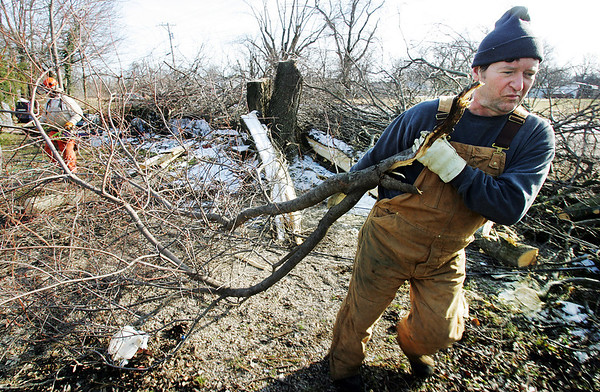 Globe/T. Rob Brown<br /> Ted Green of Sidney, Ark., a volunteer with the Rocky Bayou Baptist Association of Franklin, Ark., serving with the Southern Baptist Convention Disaster Relief from Arkansas, drags limbs from a yard on First Street in Carterville, Mo., Monday afternoon, Dec. 17, 2007. An ice storm covered the Joplin, Mo., area and left many homes without power for a week or more.