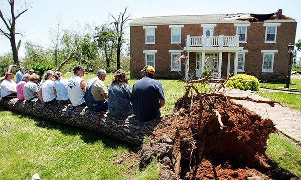 The Joplin Globe/T. Rob Brown<br /> Newtonia, Mo., residents sit on a tornado-downed tree outside the Ritchey Mansion in Newtonia as they wait for Congressman Roy Blunt to arrive Monday afternoon, May 12, 2008. The mansion suffered damage to all three chimneys, the roof, and more.
